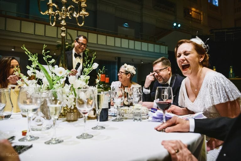 Bride laughing wildly during wedding speeches