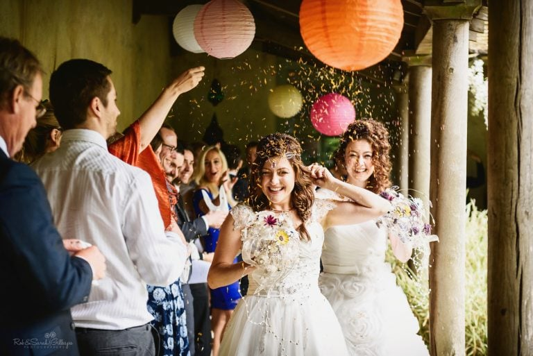 Two brides run up aisle as confetti is thrown over them
