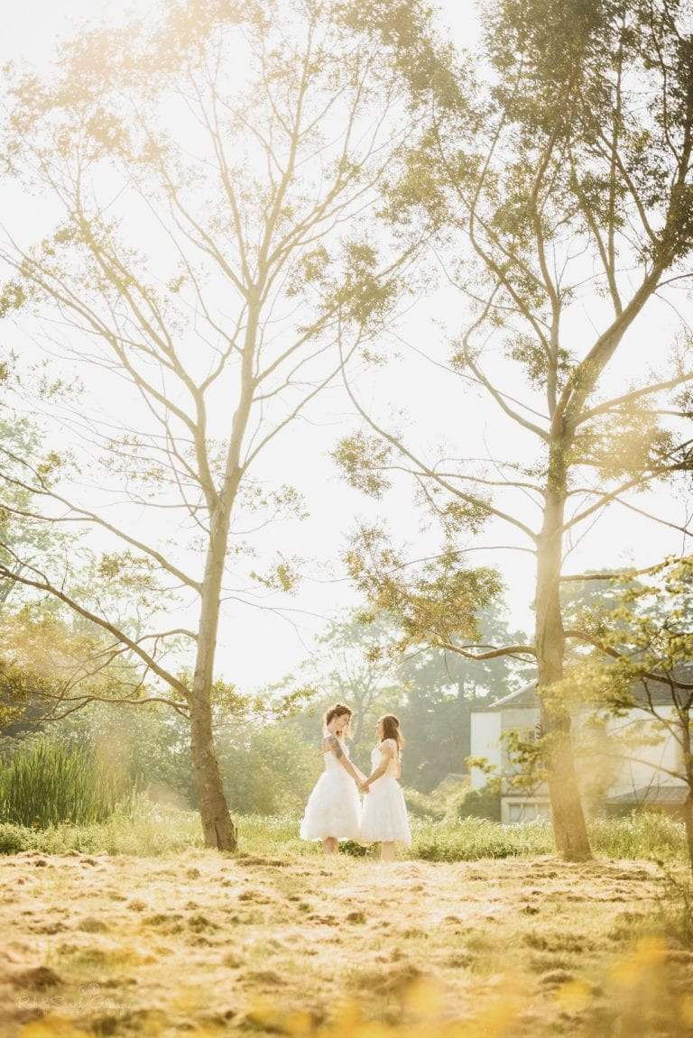 Two brides holding hands beneath two tall trees