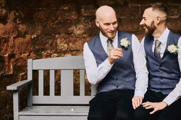 Two grooms laughing as they sit together on bench
