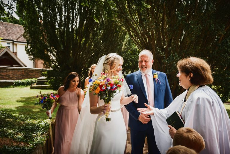 Vicar greets bride and father as they arrive at church wedding ceremony