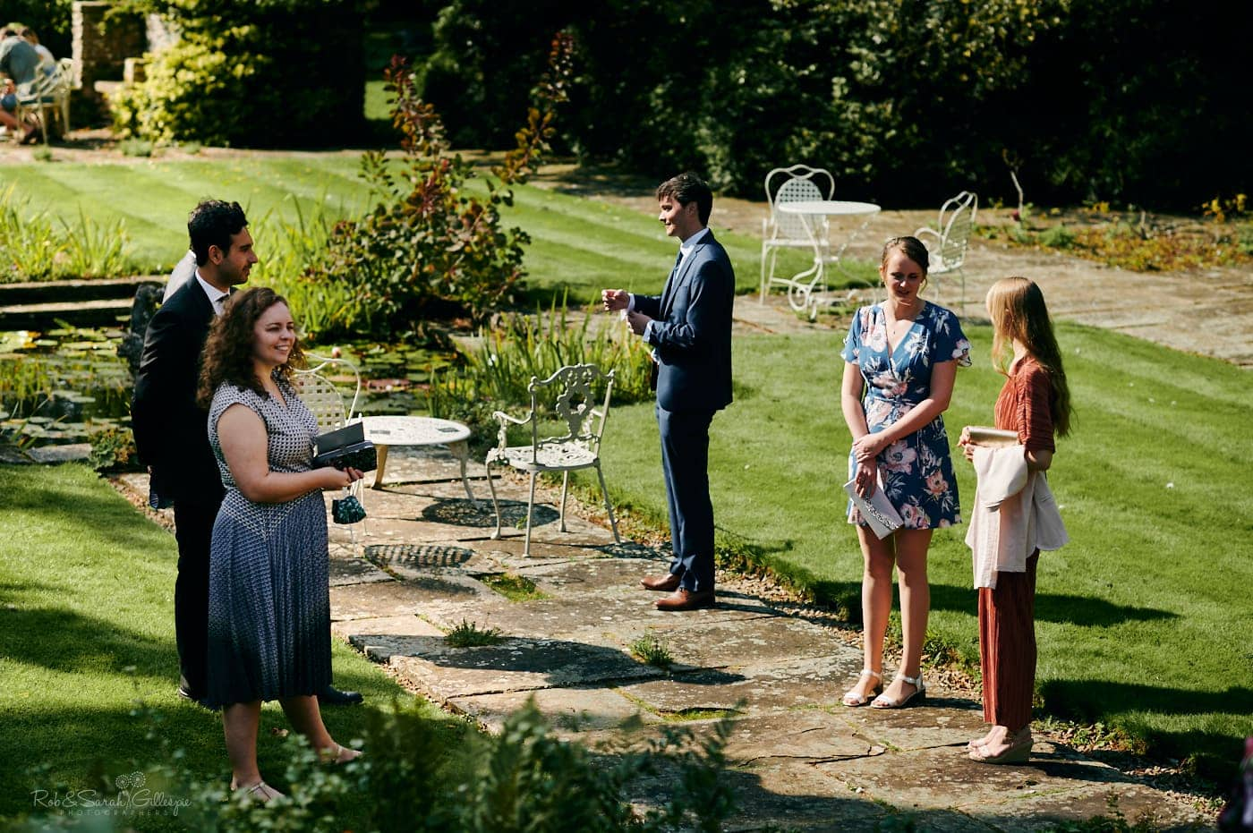 Guests chat in gardens at Mallory Court before small wedding ceremony