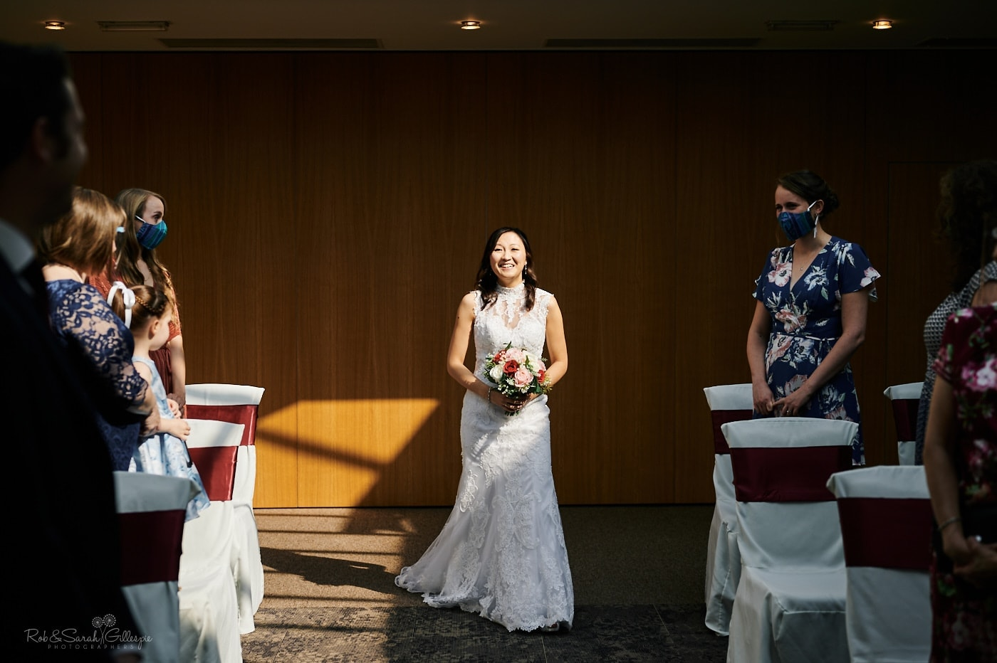 Bride enters Covid wedding ceremony at Mallory Court in strong light