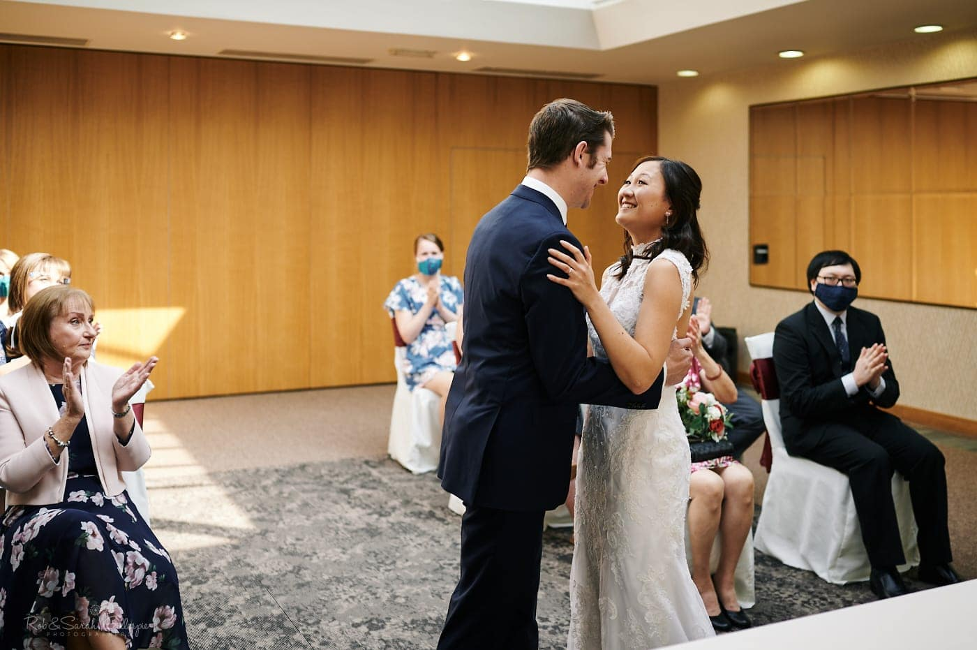Bride and groom smiling after first kiss during ceremony