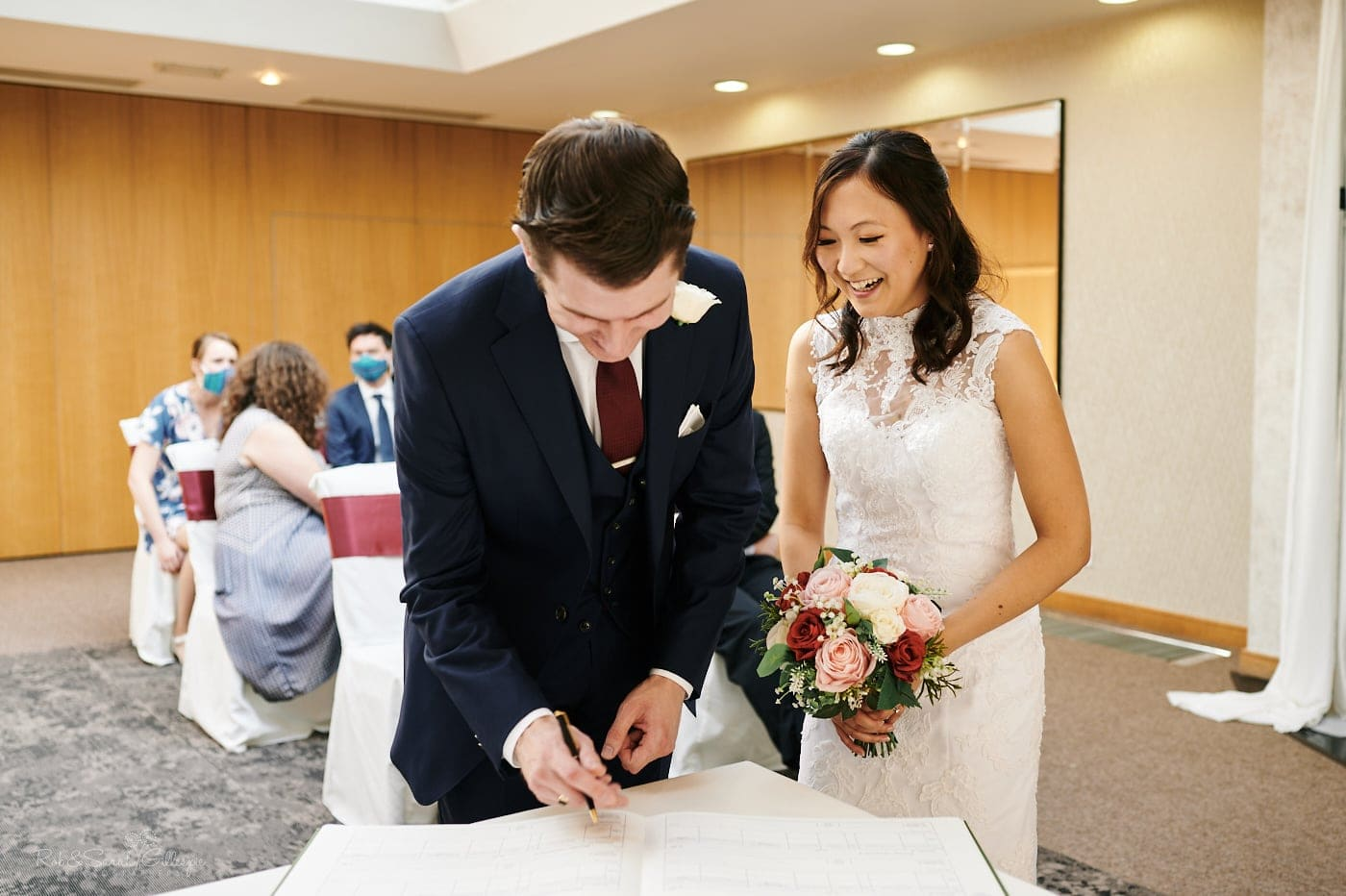 Bride and groom sign marriage register at Mallory Court wedding