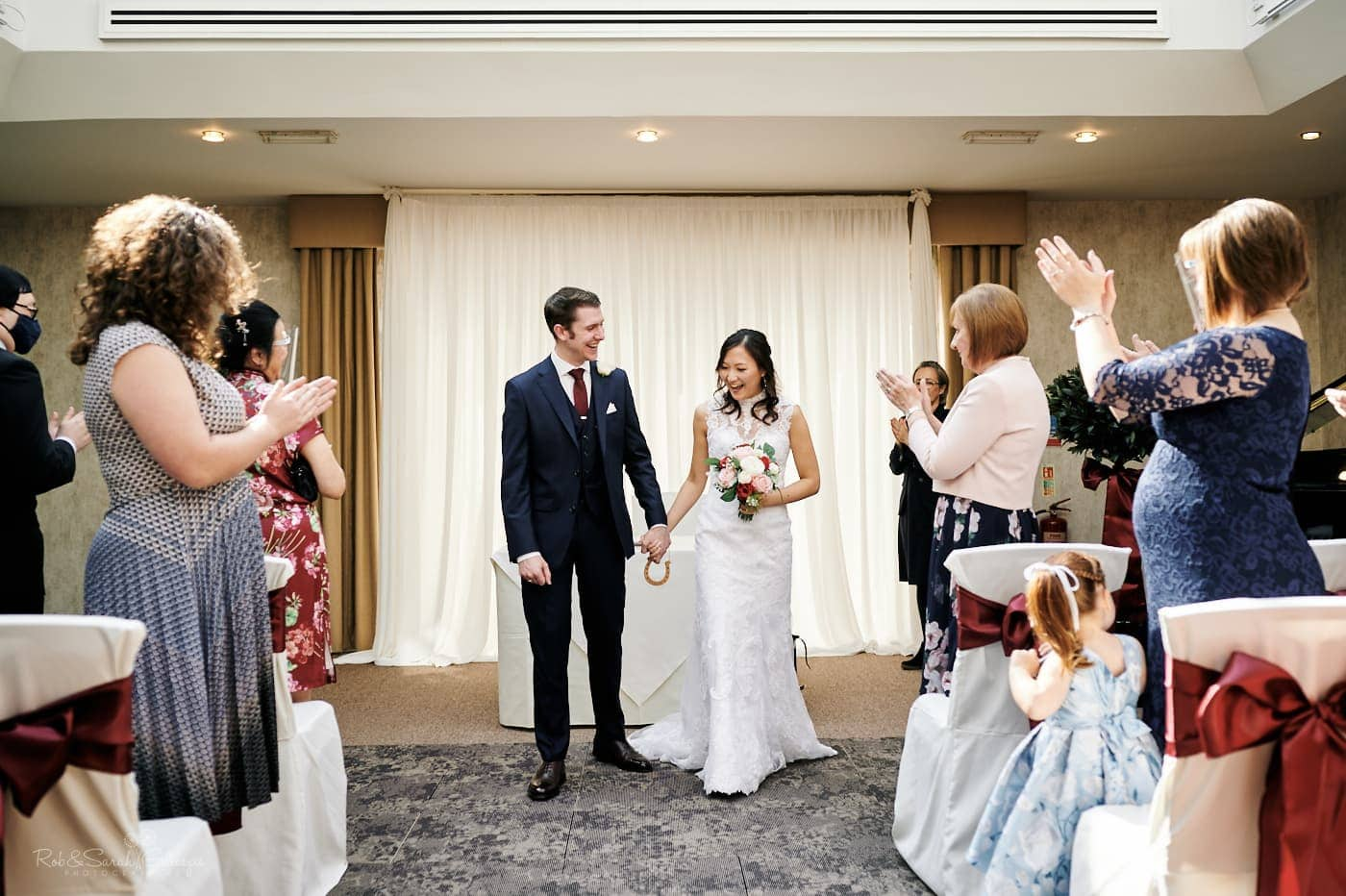 Bride and groom exit ceremony at Mallory Court as guests clap
