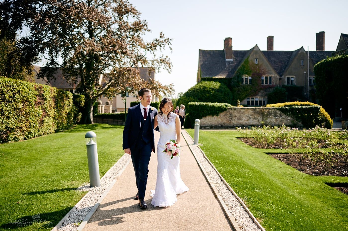 Bride and groom walk through grounds at Mallory Court small wedding