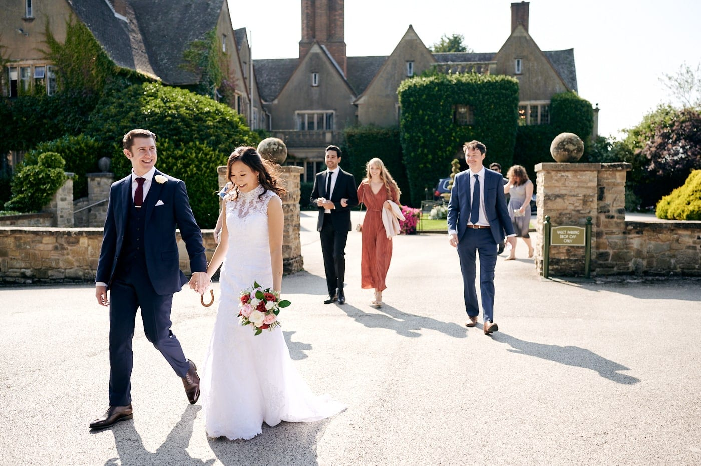 Bride, groom and guests walk through Mallory Court grounds
