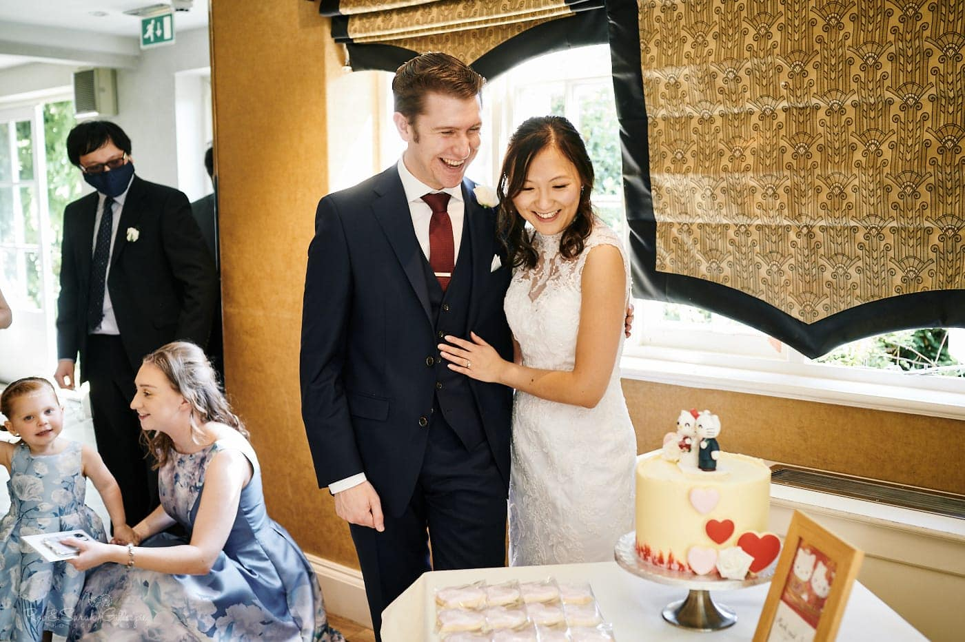 Bride and groom look at wedding cake
