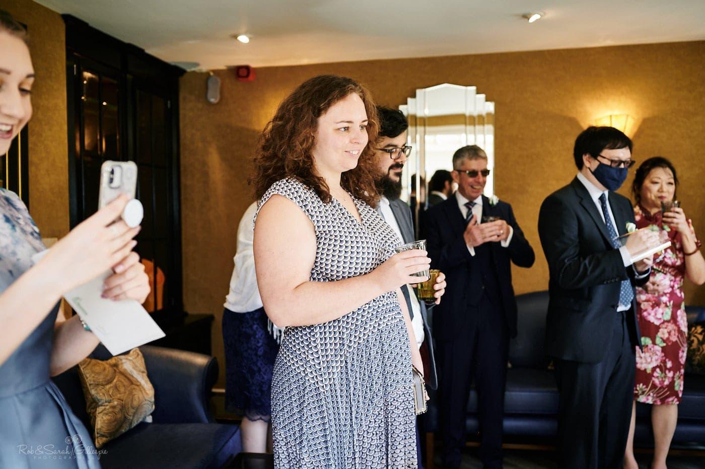 Wedding guests watch bride and groom cut cake