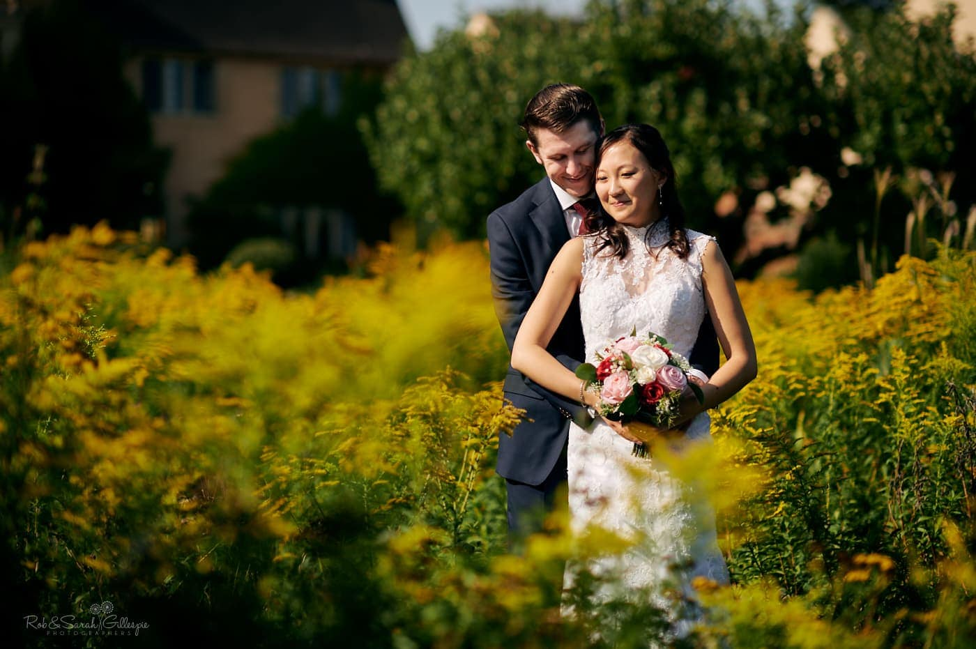 Newly married bride and groom cuddled up in beautiful gardens on sunny day