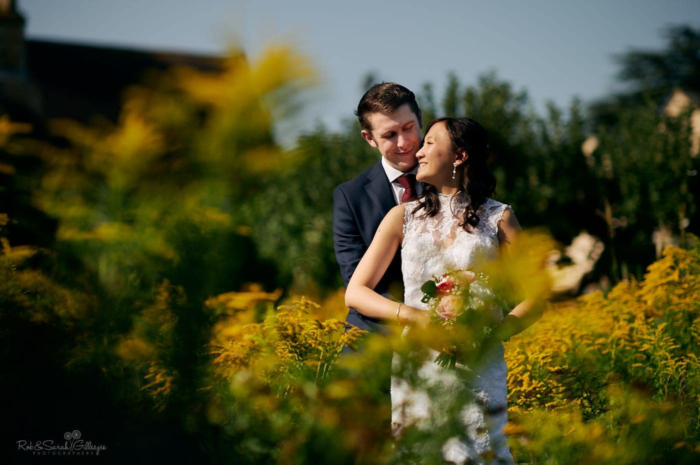 Bride and groom in Mallory Court gardens on bright sunny day