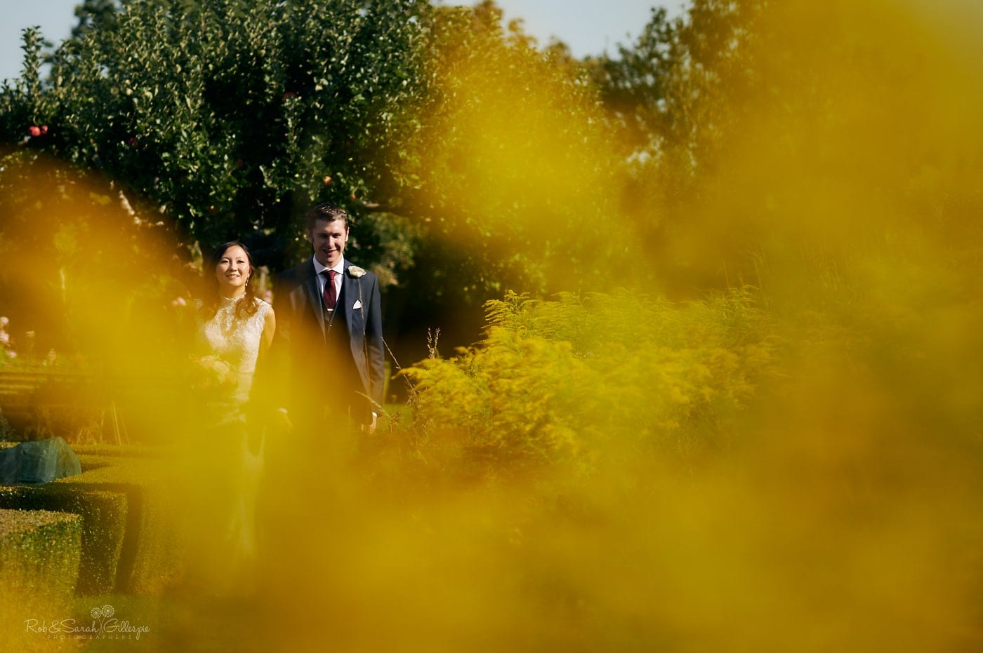 Newly married couple walk through gardens at Mallory Court on bright sunny day