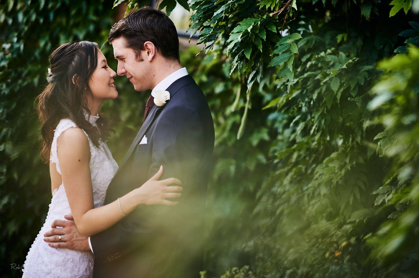 Bride and groom face to face in gardens at Mallory Court