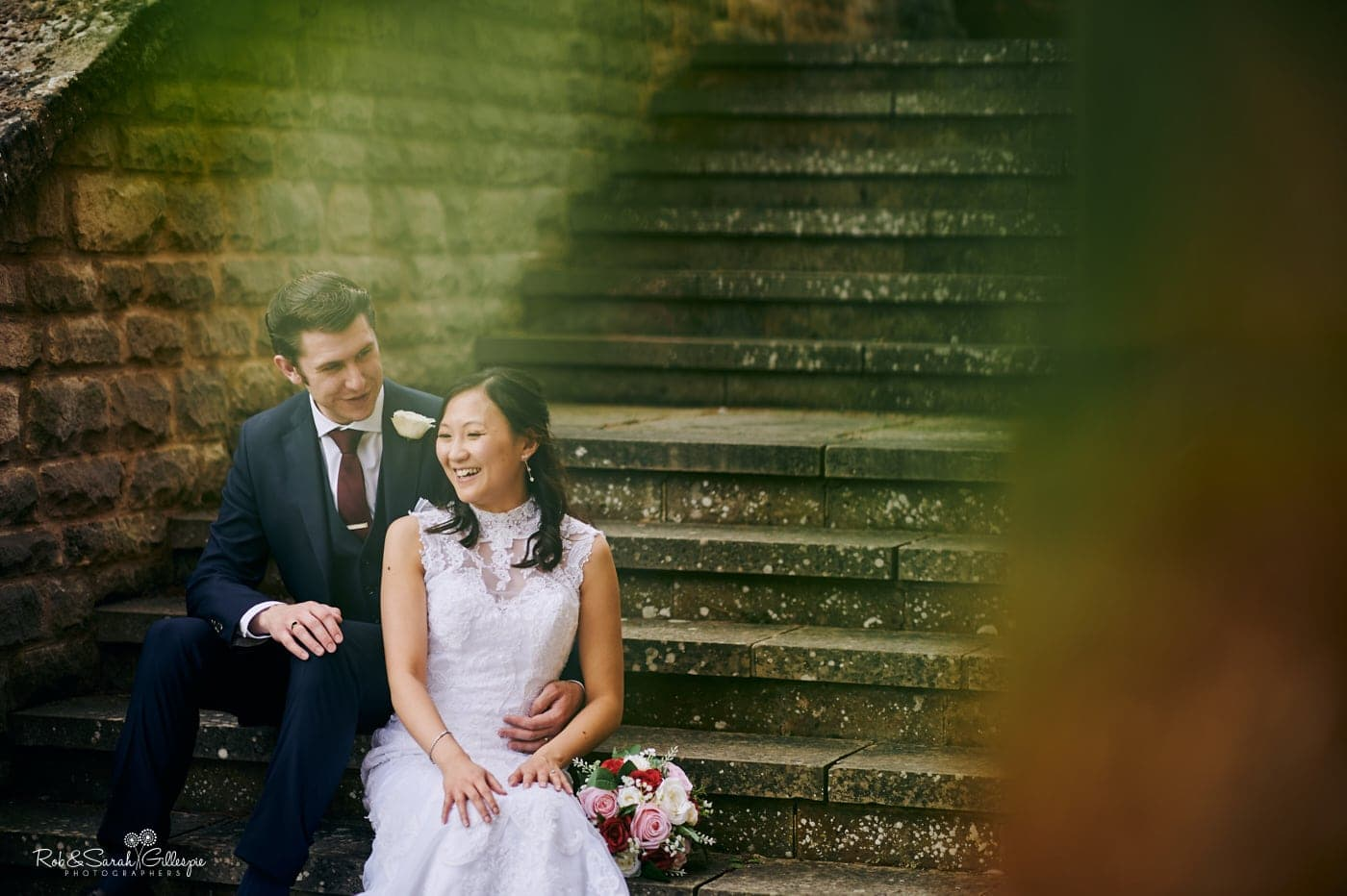 Bride and groom laughing together while sitting on steps at Mallory Court