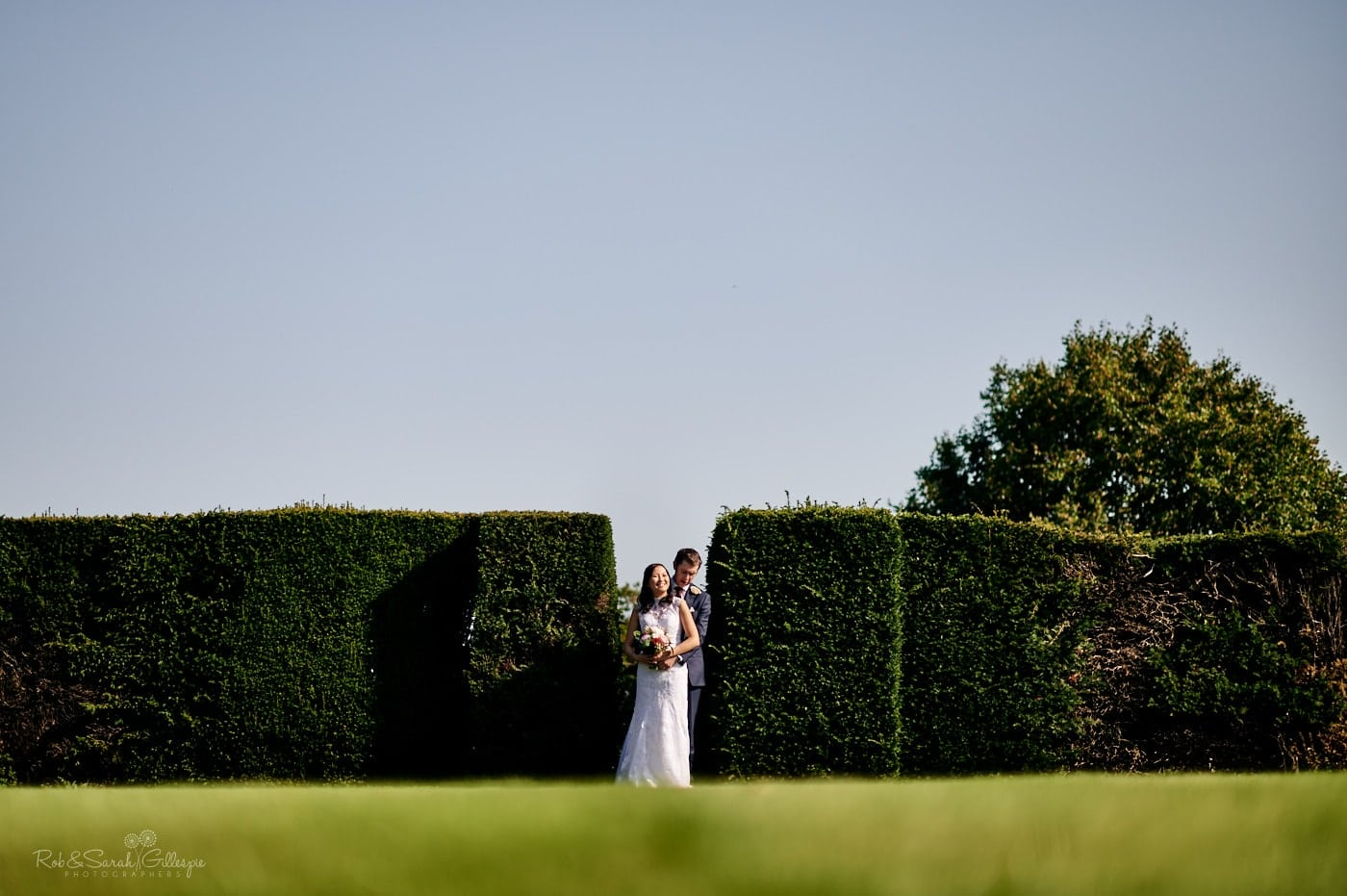 Bride and groom stand together between hedges at Mallory Court
