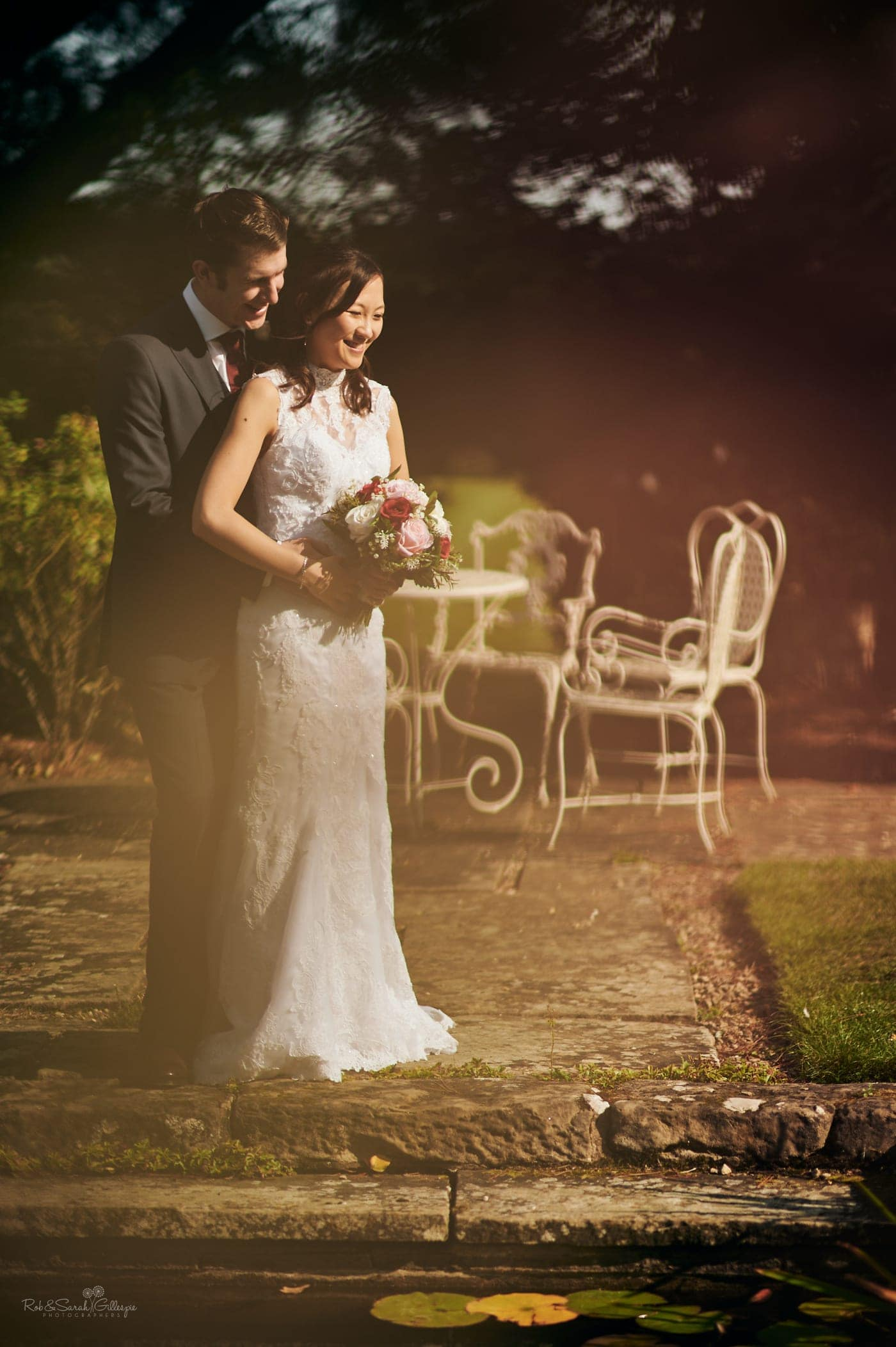 Bride and groom together in gardens at Mallory Court