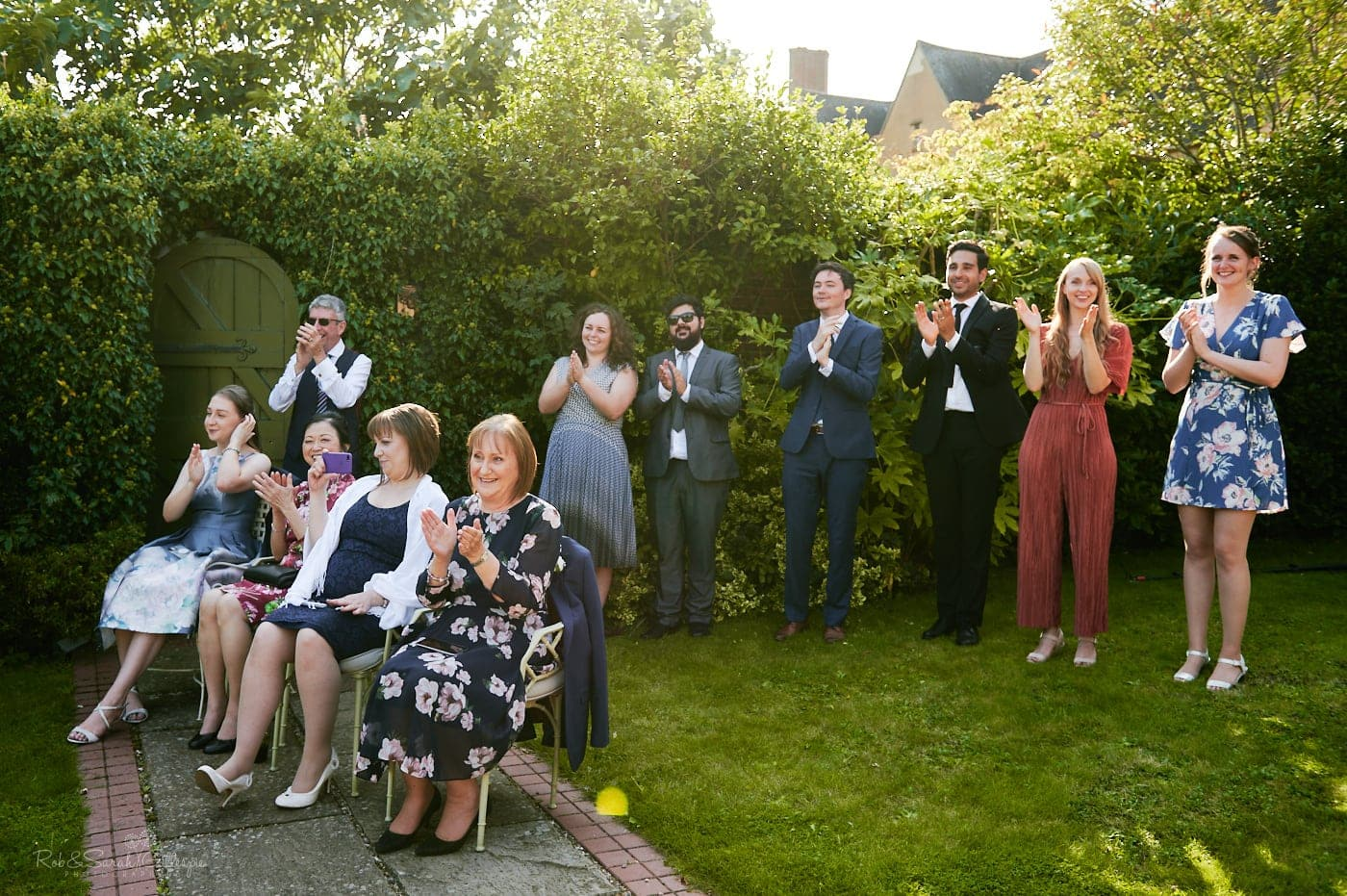 Wedding guests clap as bride and groom perform first dance outside