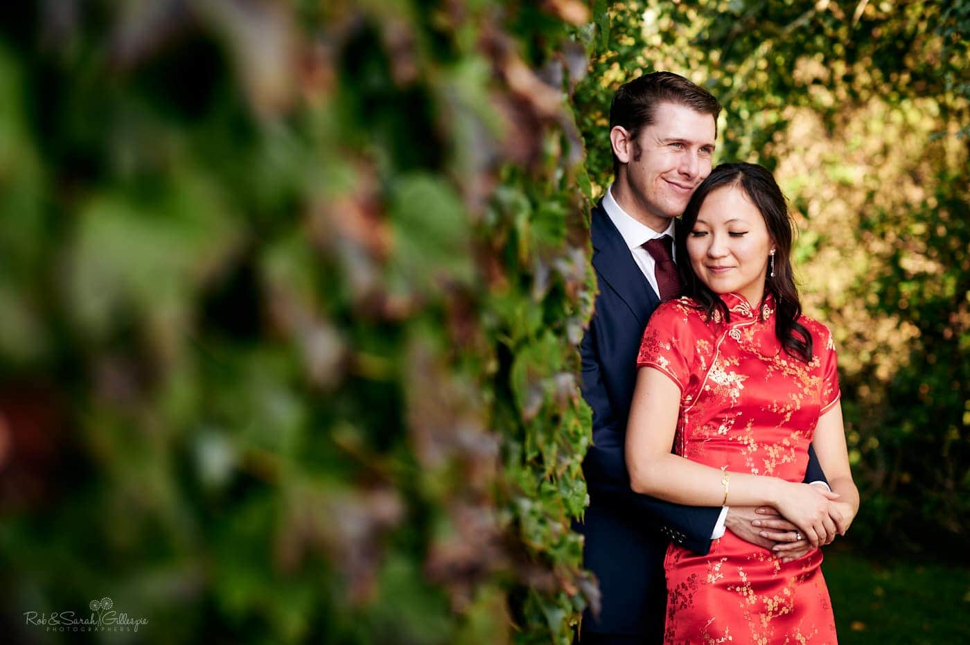 Bride in red Chinese wedding dress cuddled by groom at Mallory Court wedding