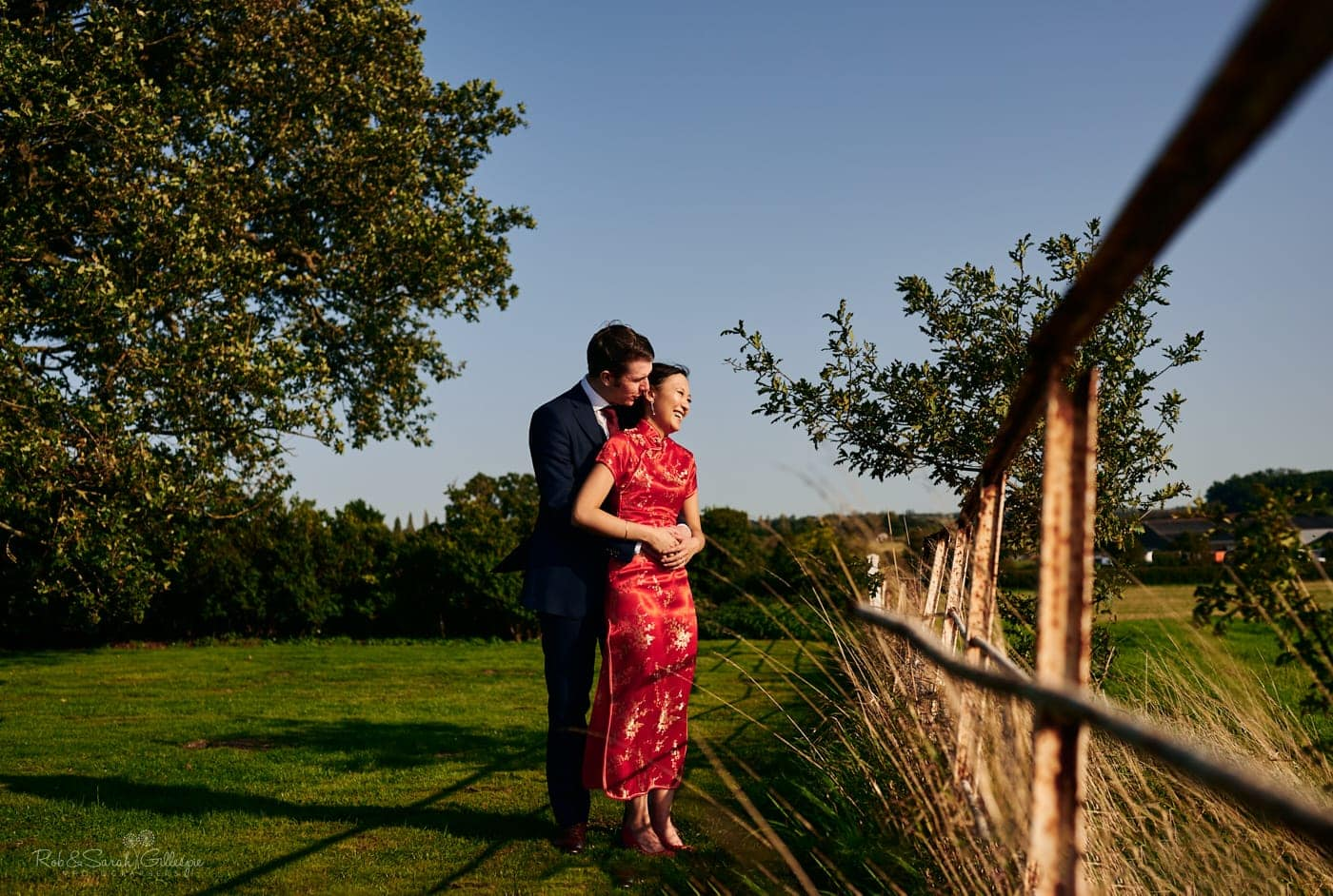 Bride and groom in Mallory Court grounds near old rusty fence