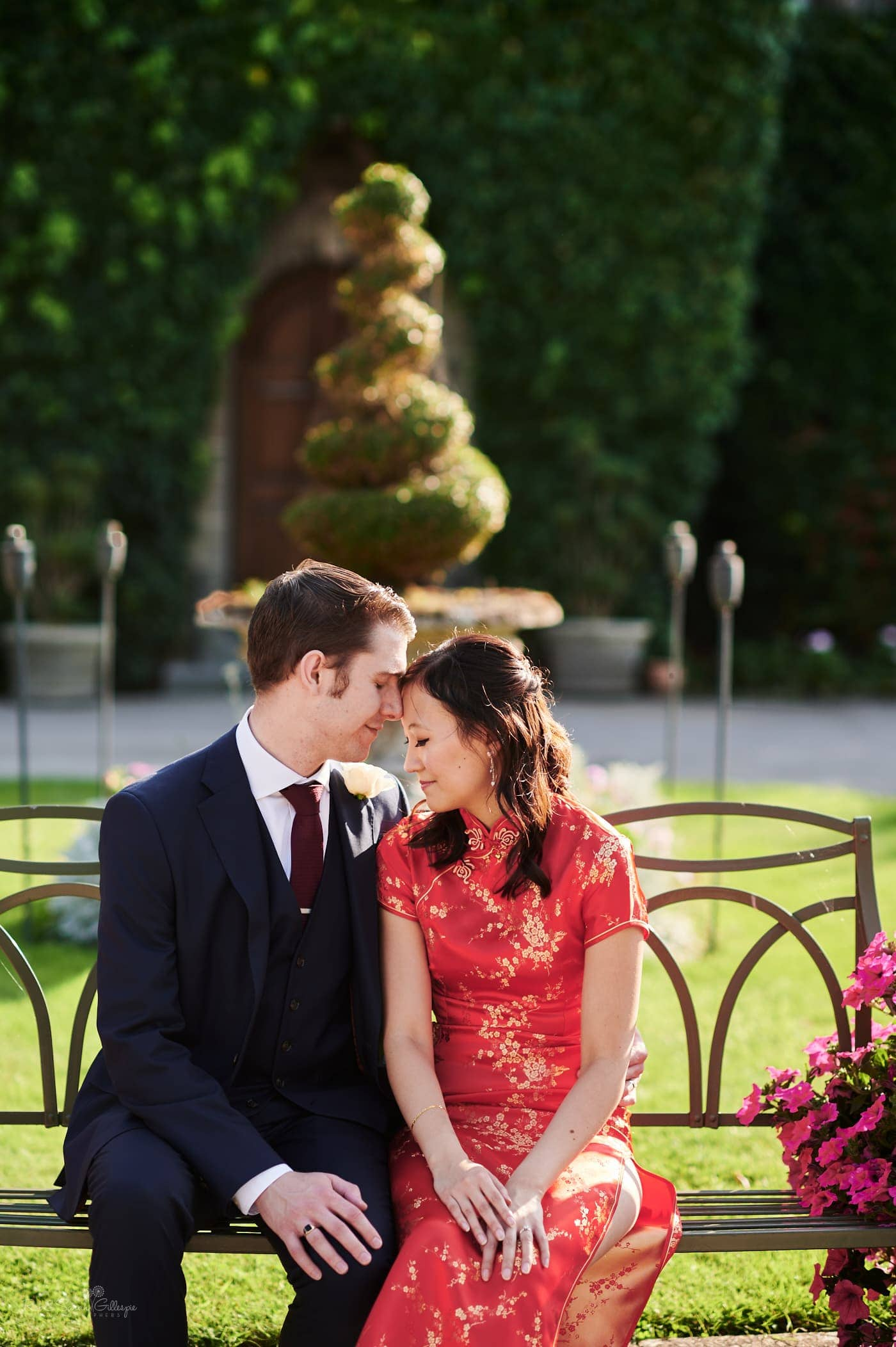 Bride in red Chinese wedding dress and groom sitting on bench at Mallory Court