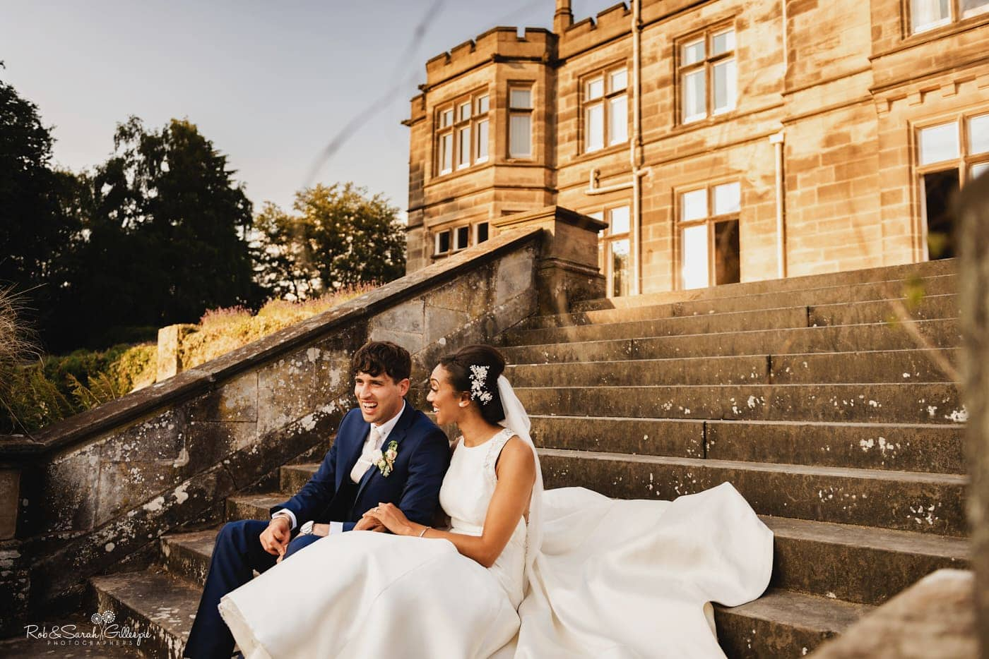 Bride and groom relaxed and laughing while sitting on steps at Hampton Manor with sunset