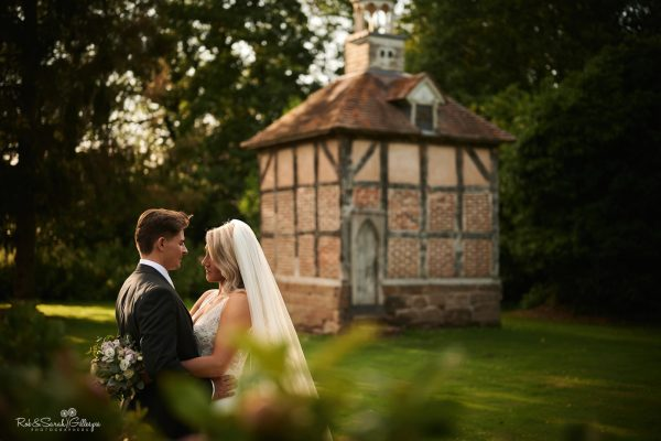 Bride and groom in grounds at Brockencote Hall with dovecote in background