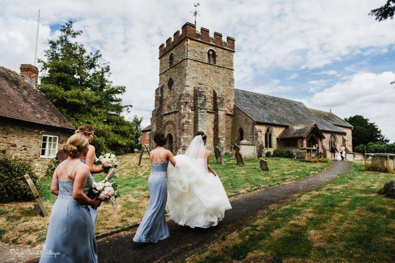 Bride and bridesmaids walk towards church at Delbury Hall