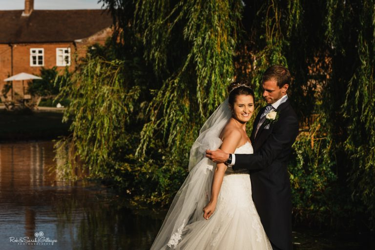 Bride and groom in grounds at Delbury Hall as wind blows veil