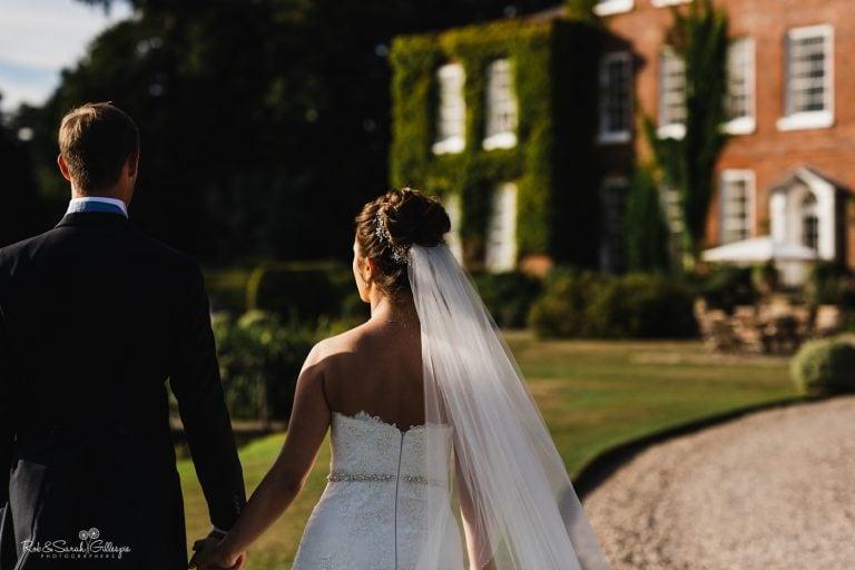 Bride and groom walk hand in hand towards Delbury Hall