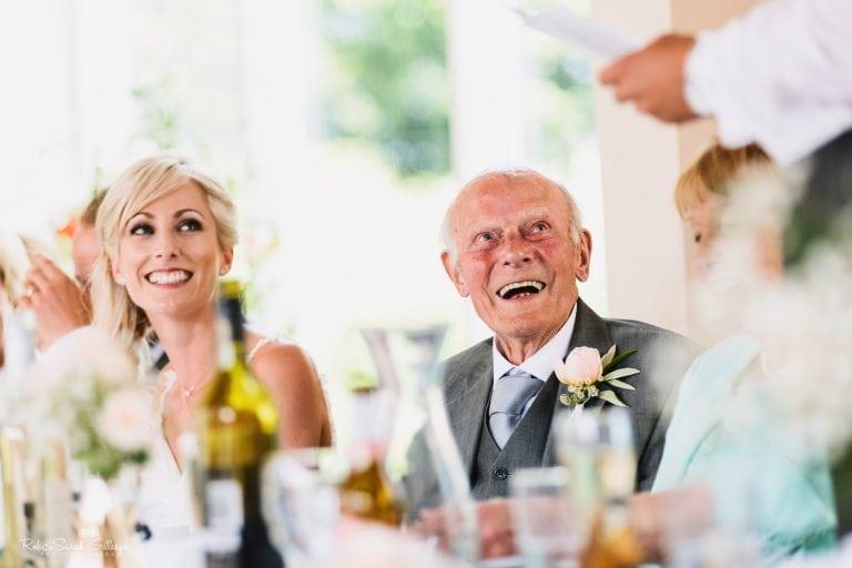 Bride and grandfather listen to speeches at Delbury Hall wedding