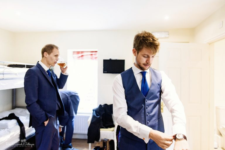 Groom gets ready for wedding while friend drinks beer