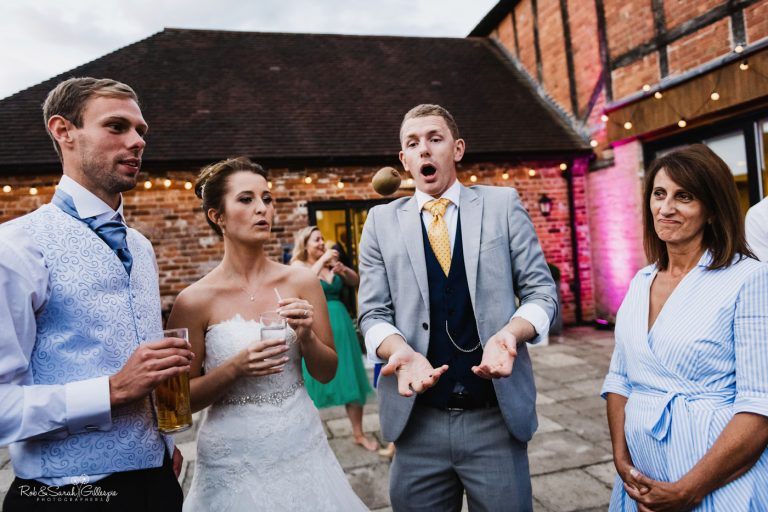 Bride and groom watch magician perform in courtyard at Delbury Hall
