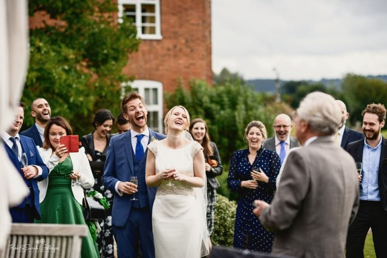 Bride, groom and guests laugh during outdoor speeches at Delbury Hall wedding