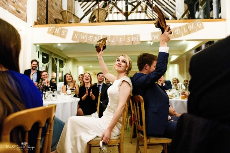 Bride and groom hold up shoes during Swedish speeches at Delbury Hall wedding