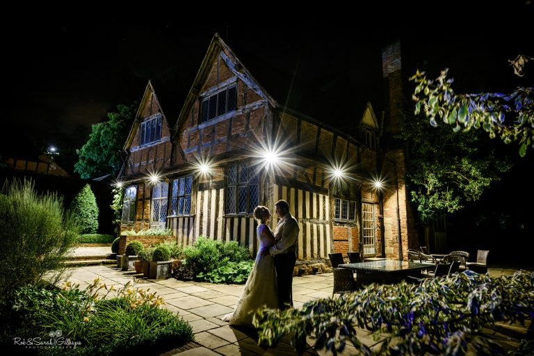 Bride and groom outside Gorcott Hall at night with venue lighting and surrounded by foliage