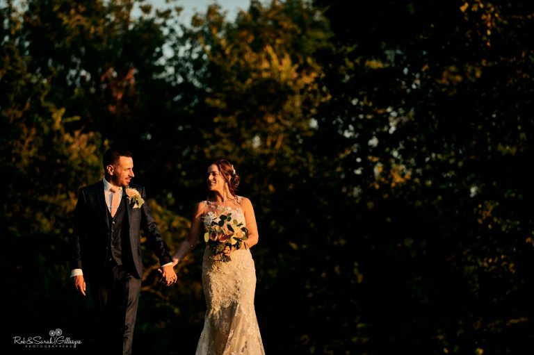 Bride and groom walking through grounds at Gorcott Hall in beautiful evening light