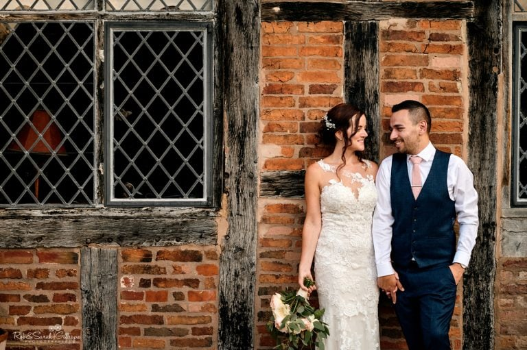 Bride and groom leaning against half timber building at Gorcott Hall