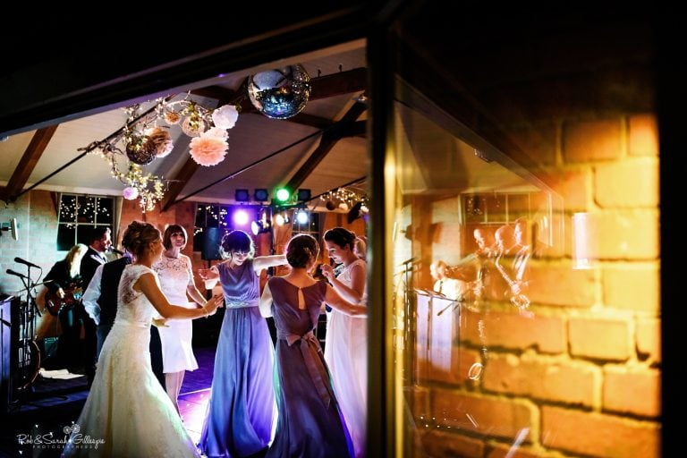 Bride and wedding guests dance as live band play