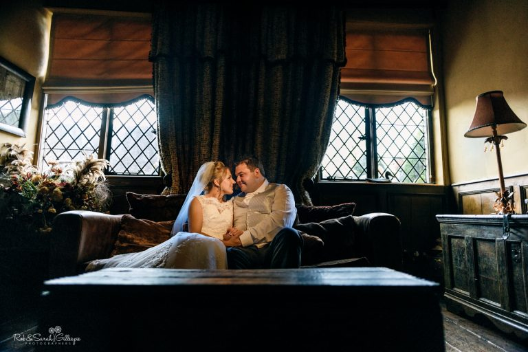 Bride and groom together on sofa inside wood panelled room at Gorcott Hall