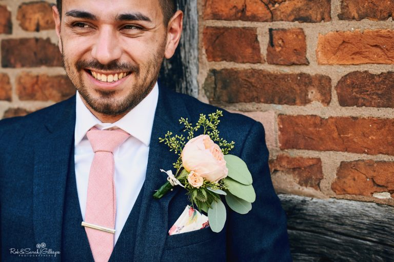 Portrait of groom leaning against half-timber building