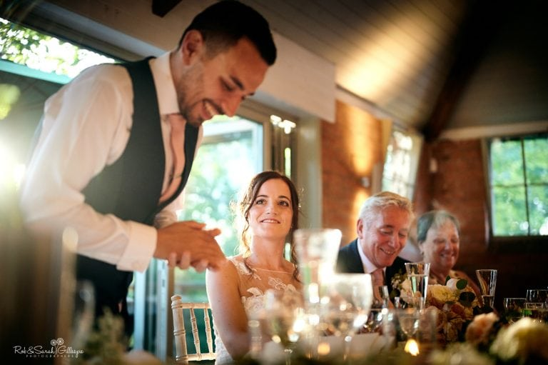 Groom gives speech at Gorcott Hall wedding as bride smiles