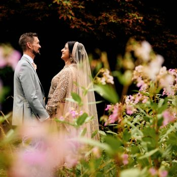 Bride in Indian wedding dress and groom in gardens at Highbury Hall surrounded by flowers