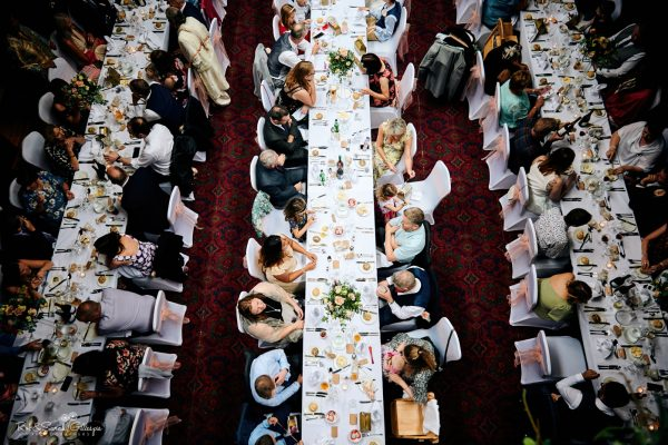 View looking down onto banquet tables with guests seated at Highbury Hall wedding