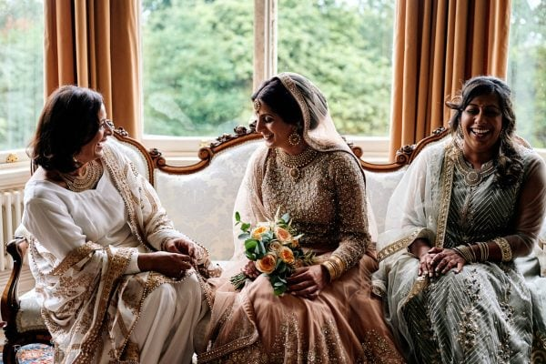Bride and friends in indian wedding dresses laughing together while sitting on couch