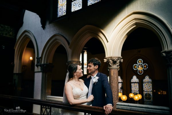 Bride and groom on balcony at Highbury Hall in strong light