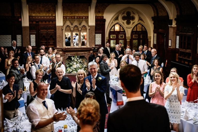 Wedding guests clap as bride and and groom enter room for wedding meal