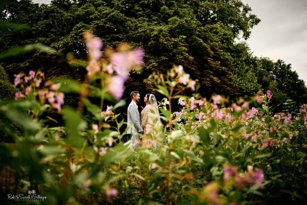 Newly married couple in lush gardens, surrounded by purple flowers
