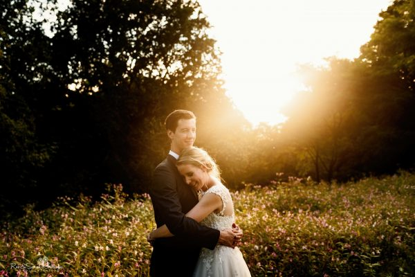 Bride and groom hug during beautiful sunset in gardens