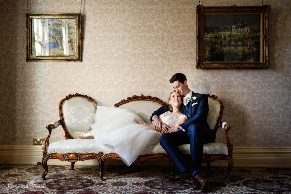 Bride and groom cuddle on old sofa in room at Highbury Hall